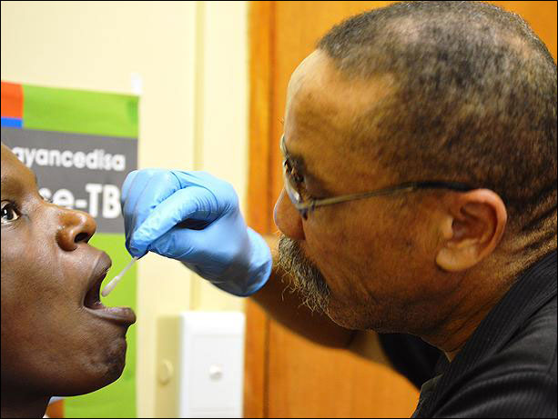 Medical staffer collects patient's swab sample for TB testing