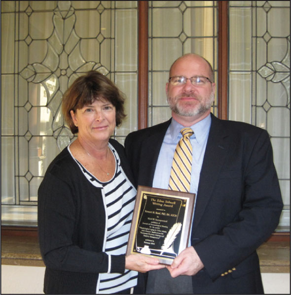 Journal of Gerontological Nursing Editor Kathleen C. Buckwalter, RN, PhD, FAAN (left), Presents Stewart M. Bond, PhD, RN, AOCN, with a Plaque for the Edna Stilwell Writing Award for His February 2010 Article.