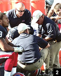 Figure 2: Andrew Cappuccino, Bud Carpenter, and Chris Fischetti evaluate a Buffalo Bills player for cervical spine injury on sidelines