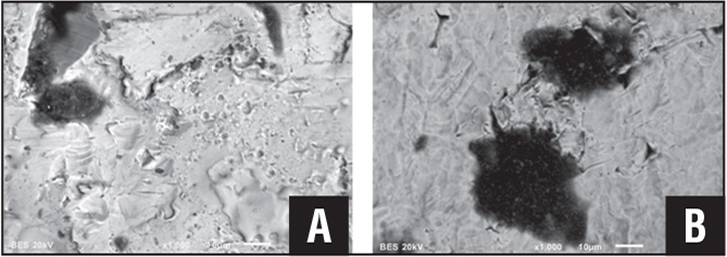 Corrosion pits associated with the presence of biofilm. Image from the rods shown in Figure 1 (A). The true surface of the rod that was obscured by the film. Small nodules are cellular remnants and as determined by their dark color indicating light elements. Surface cracking can be seen where biofilm has been removed (B).