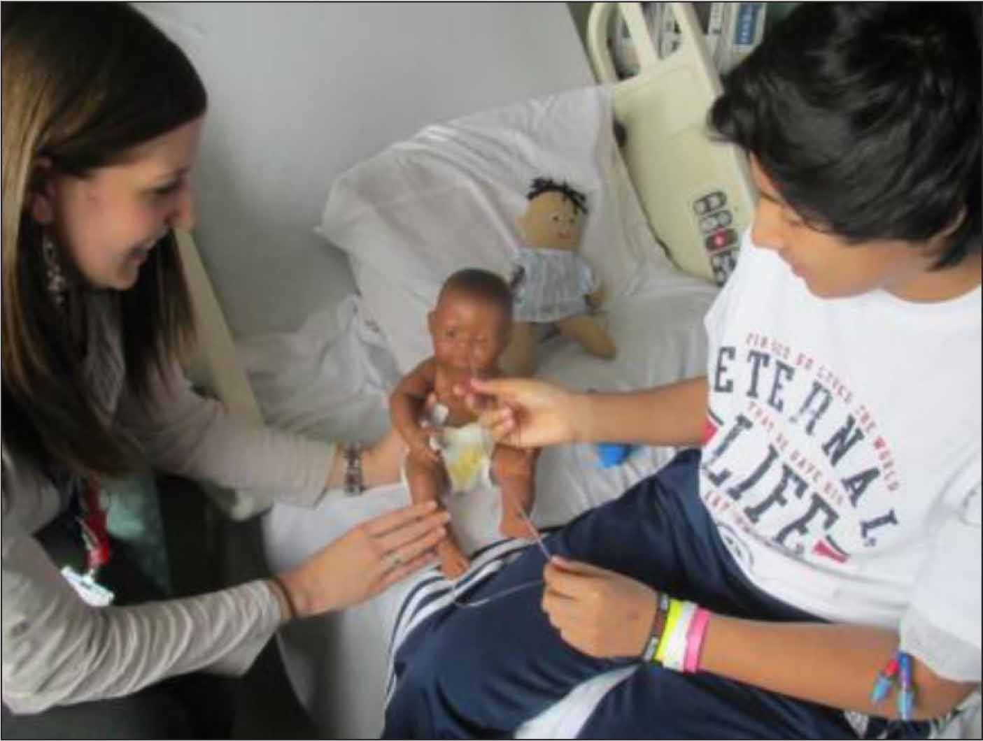 Child life specialist and co-author, Kelsey Mora, educating a 14-year-old about a previously placed peripherally inserted central catheter line and nasogastric tube.