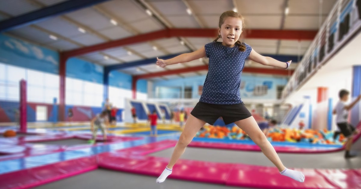 Young girl jumping on trampoline at trampoline park